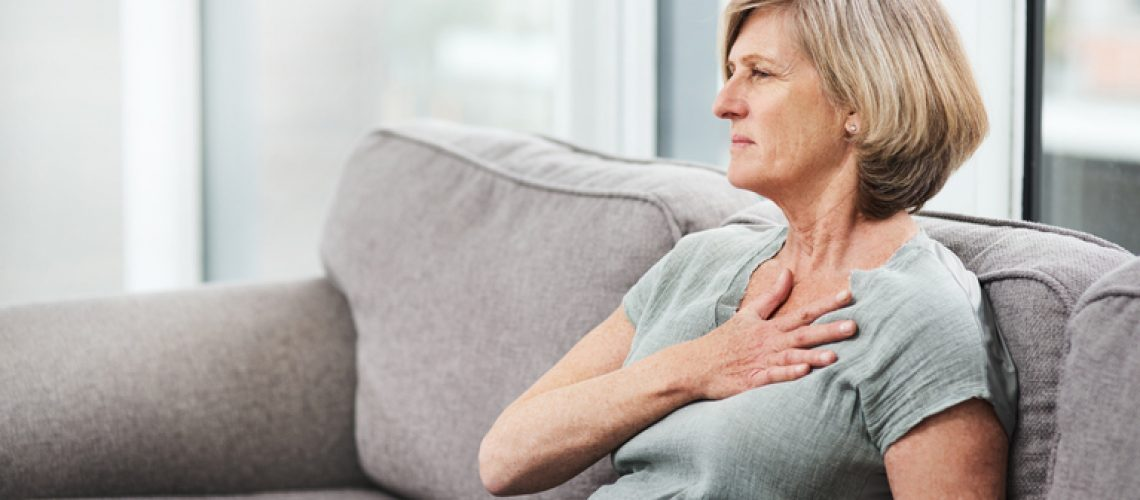 Shot of a senior woman suffering from chest pain while sitting on the sofa at home